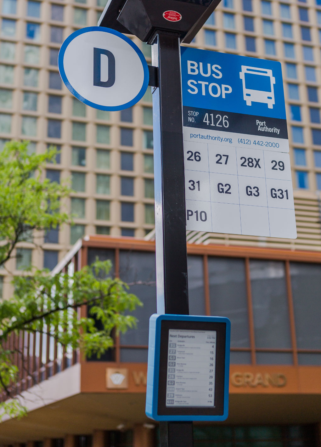 Solar-powered 10-inch Digital Bus Stop ePaper display showing real-time transit information with Brasco SolStop installed in Pittsburgh.