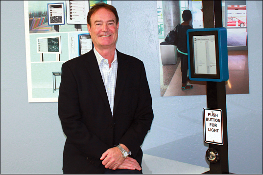 Rick Wood with the solar-powered Connectpoint Digital Bus Stop; Joshua Molina/Pacific Coast Business Times photo